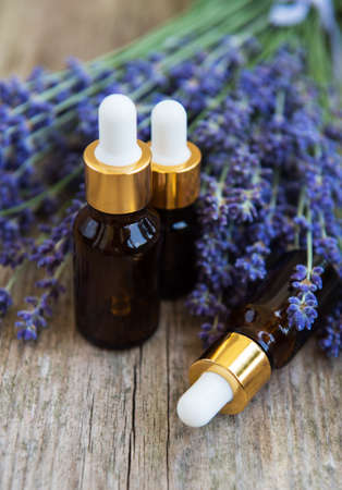 Natural lavender oils and lavender flowers on a old wooden table