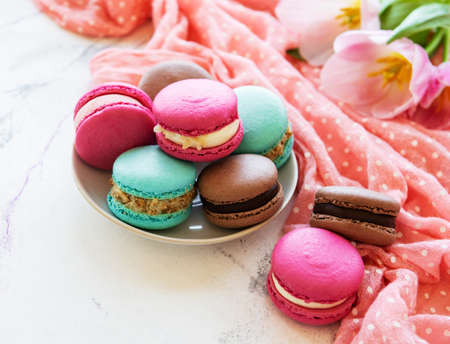 Colorful macaroons and tulips on a white marble  background