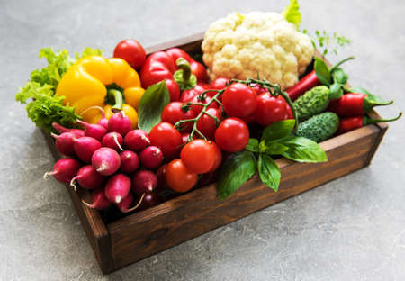 Box with  different raw vegetables on a old concrete background