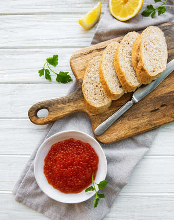 Red caviar in bowl and bread for sandwiches on a old wooden table