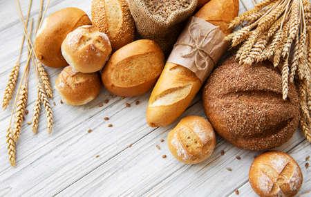 Surtido de pan horneado sobre fondo de madera blanca