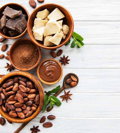 Natural cocoa powder, cocoa butter and cocoa beans on a wooden background