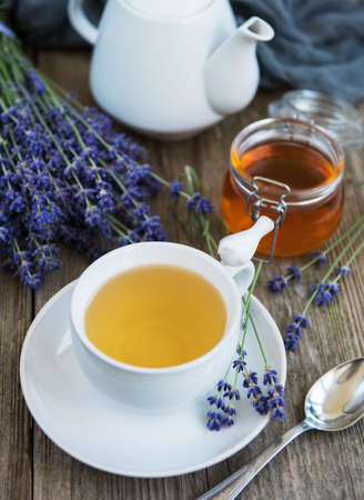 Cup of tea and honey with lavender flowers on a old wooden table Reklamní fotografie - 123115217