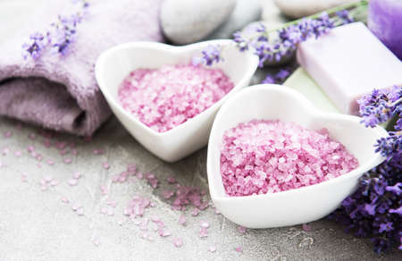 Heart-shaped bowl with sea salt, soap and fresh lavender flowers on a concrete background