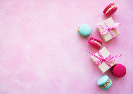 Colorful macaroons and gift boxes on a pink concrete background