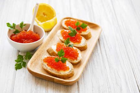 Red caviar in bowl and sandwiches on a old wooden table