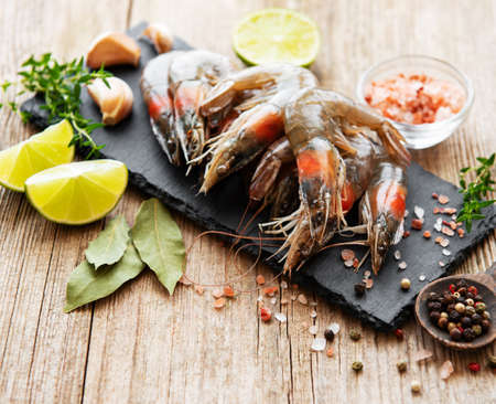 Fresh raw  prawns and spices on  wooden table