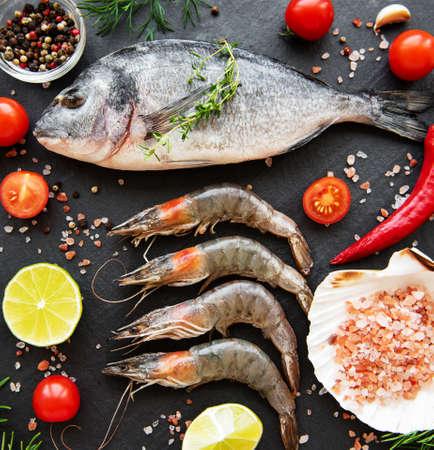Fresh raw  prawns, dorado fish and spices on  black stone background