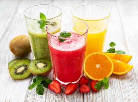 Gesunde Frucht-Smoothies und frische Früchte auf einem alten Holztisch