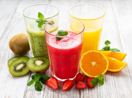 Healthy fruit smoothies and fresh fruits on a old wooden table