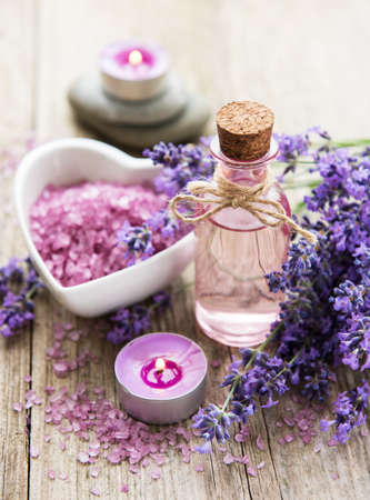 Heart-shaped bowl with sea salt, oil and fresh lavender flowers on a old wooden background Stock Photo