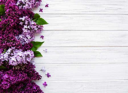 Lila Frühlingsblumengrenze auf einem weißen hölzernen Hintergrund