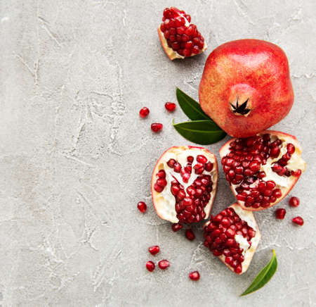 Ripe pomegranate fruits on grey concrete background