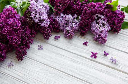 Lila Frühlingsblumengrenze auf einem weißen hölzernen Hintergrund Standard-Bild