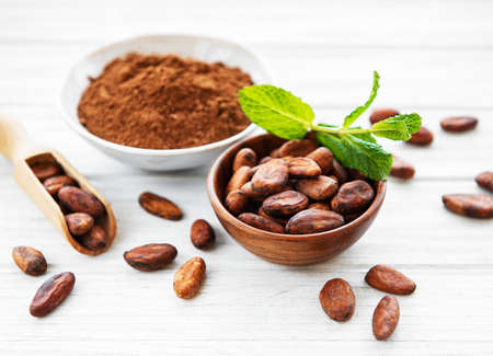 Bowl with Cocoa powder and beans on a white wooden  background