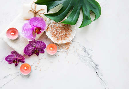 Natural spa ingredients with orchid flowers on a white marble background