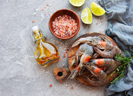 Fresh raw prawns and spices on grey concrete background