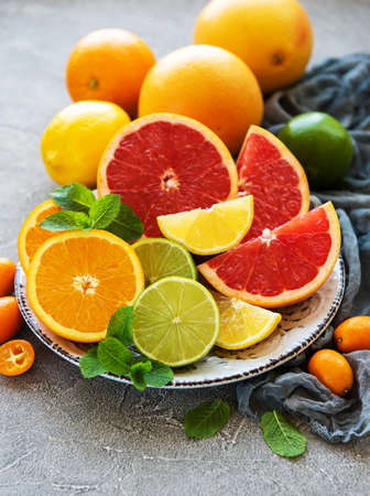 Plate with citrus fresh fruits on a concrete background