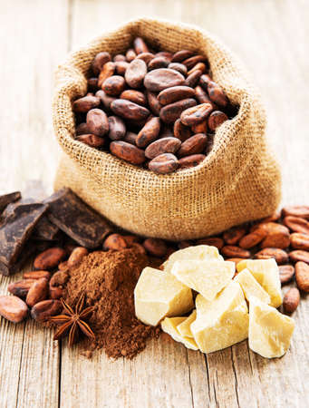 Natural cocoa beans, powder, chocolate and butter on a old wooden background