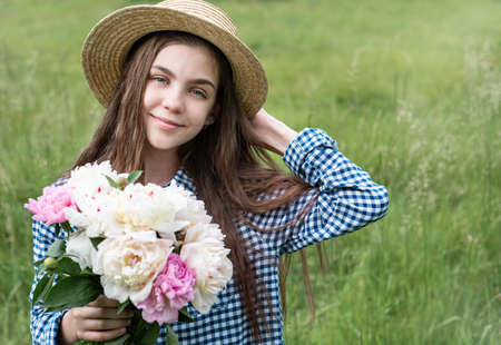 Girl in a summer field with a straw hat and a bouquet of peonies