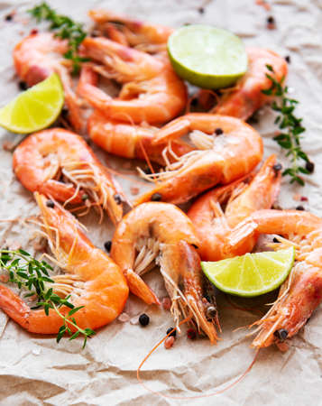 Shrimps served with lemons and spices on a paper background Stockfoto