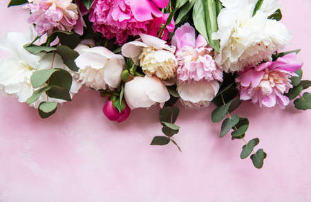 Background with pink peonies on a pink concrete background