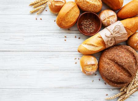 Auswahl an gebackenem Brot auf weißem Holzhintergrund Standard-Bild