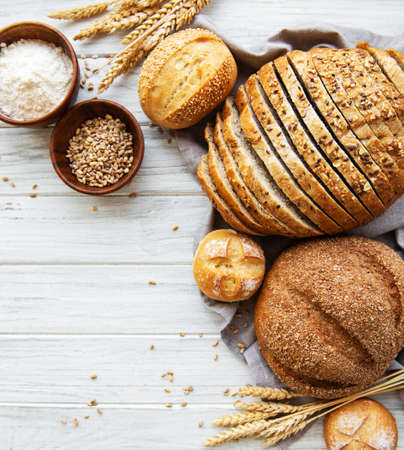 Assortment of baked bread on white wooden background