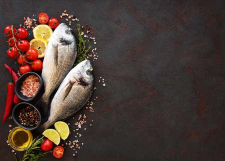 Frischer Fischdorado. Dorado und Zutaten zum Kochen auf einem Tisch.