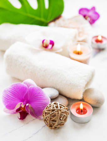 Natural spa ingredients with orchid flowers on a white marble