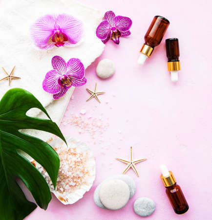 Natural spa ingredients with orchid flowers on a pink concrete