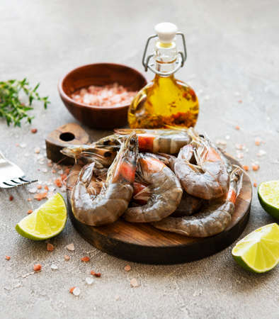 Fresh raw  prawns and spices on  grey concrete