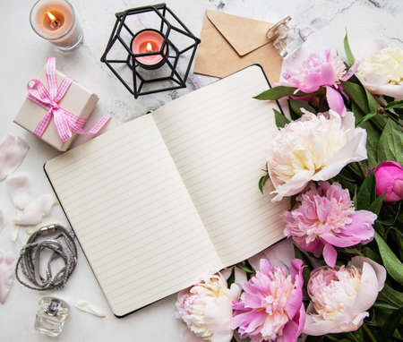 Flat lay blogger or freelancer workspace with a  notebook, pink peonies on a white wooden table