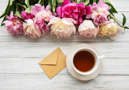 Cup of tea and pink peonies on a old wooden table Stock Photo