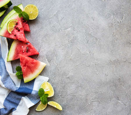 Watermelon  with limes on a concrete background 写真素材