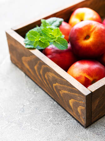 Box with fresh nectarines on a stone background