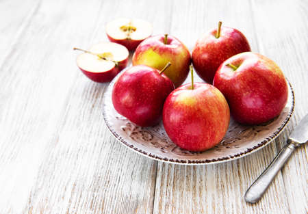 Fresh red apples on a old white wooden background