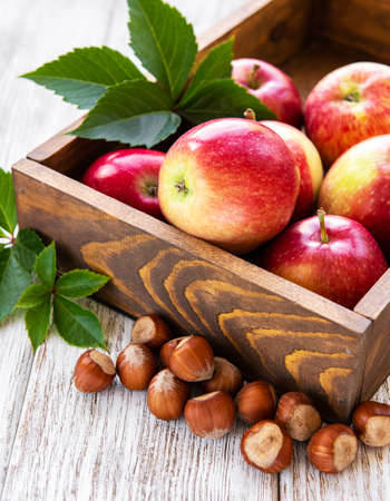 Composition with apples, hazelnuts and leaves on a old wooden table 写真素材 - 128906531