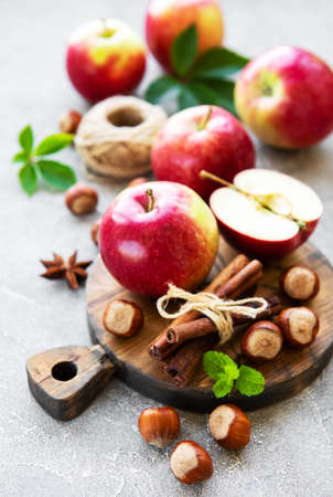 Fresh apples, hazelnuts and cinnamon on a concrete background