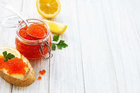 Glass jar of red caviar and snack with caviar