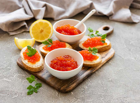 Red caviar in bowl and sandwiches on a grey concrete background Stockfoto