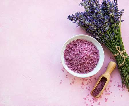 Flat lay composition with lavender flowers and natural sea salt on pink concrete background Фото со стока