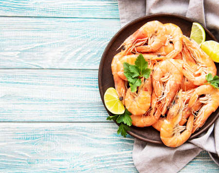 Shrimps served with lemons and spices on a wooden  background