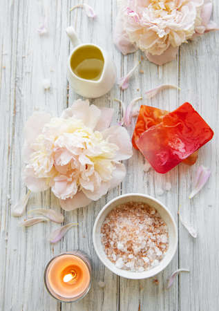SPA concept: composition of spa treatment with natural sea salt, aromatic oil and peonies flowers