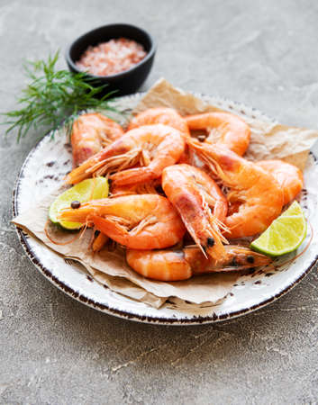 Shrimps in plate with lemons on a grey concrete background