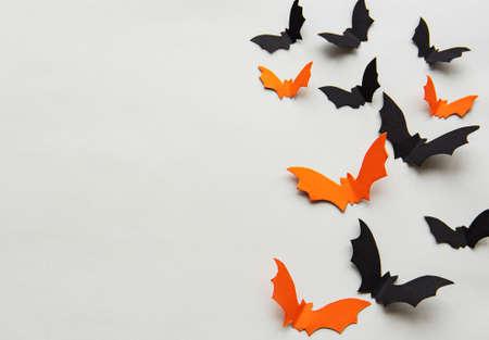 halloween  concept - black and orange paper bats flying over grey background