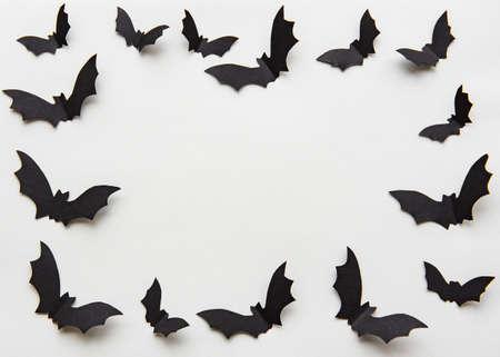 halloween  concept - black paper bats flying over grey background