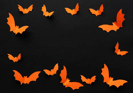 halloween  concept - orange paper bats flying over black background Stock Photo