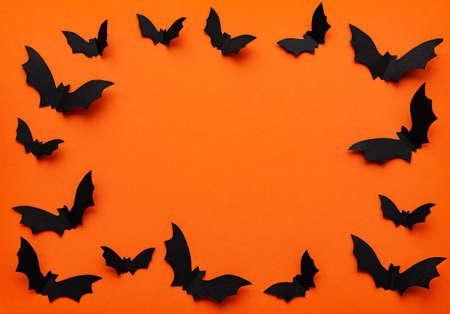 halloween  concept - black paper bats flying over orange background