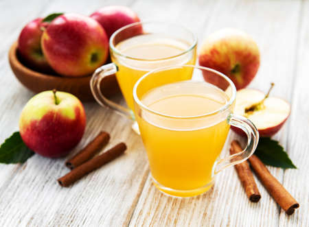 Apple cider with cinnamon sticks on a old wooden table Banco de Imagens